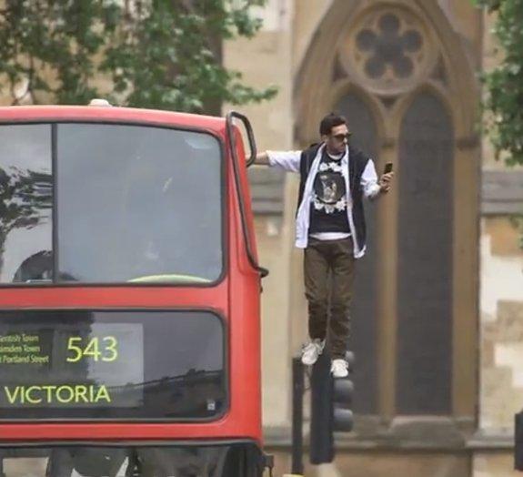 Ilusionista levita ao lado de tradicional ônibus de dois andares em Londres
