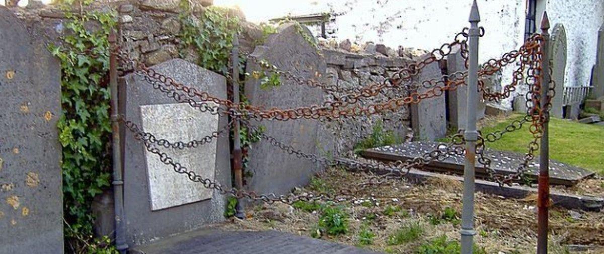 Qual será o motivo de esta sepultura ficar rodeada por estacas e correntes?