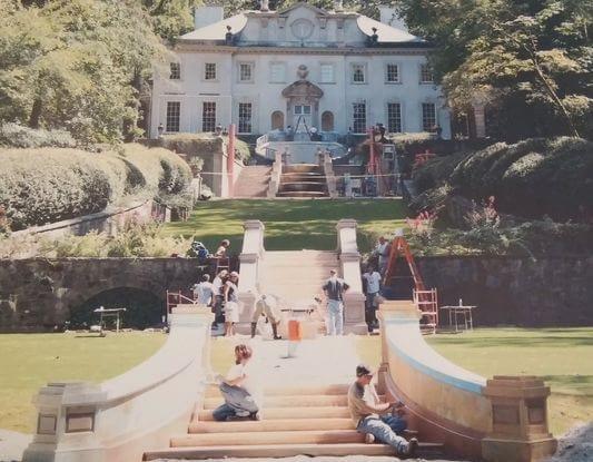 Foto em exposição mostra cenas dos bastidores de Jogos Vorazes: Em Chamas, com a produção construindo escadarias em frente à casa.