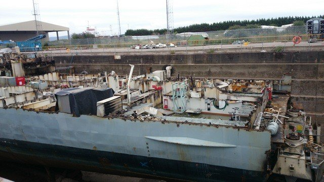 Homem fotografa figura sinistra em interior de embarcação abandonada