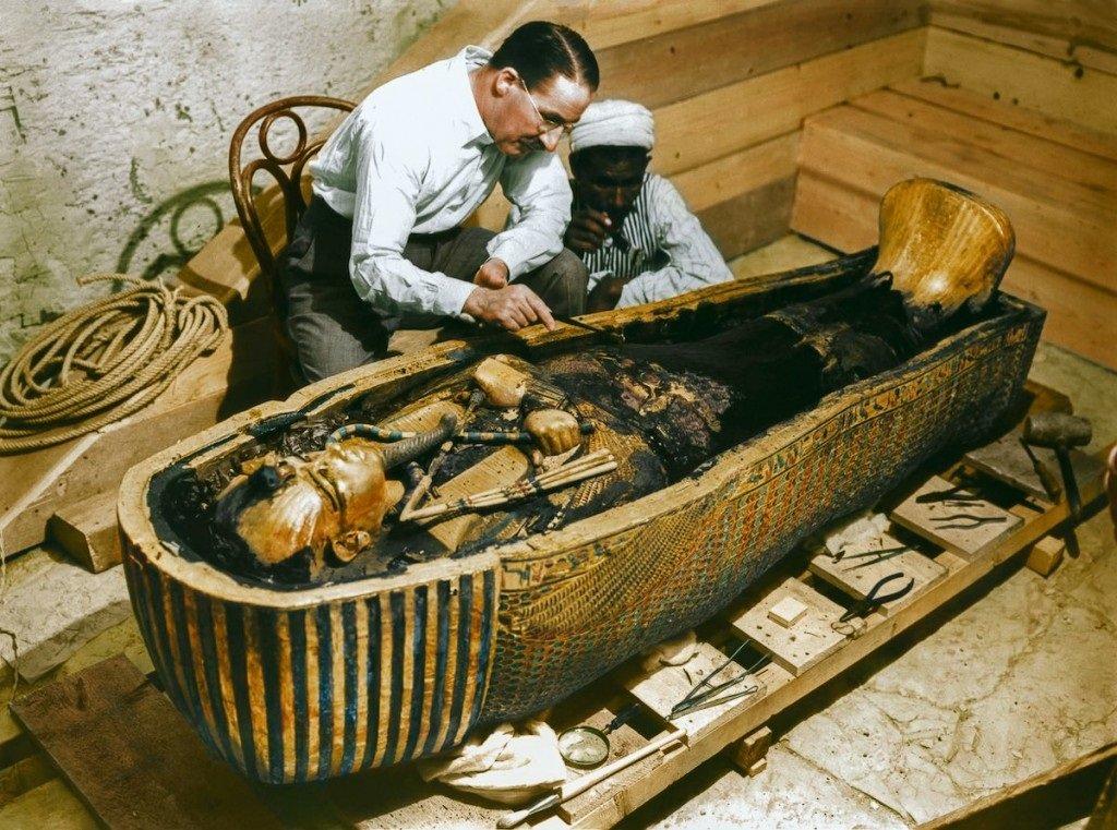 Carter examina o sarcófago do faraó ao lado de um ajudante local